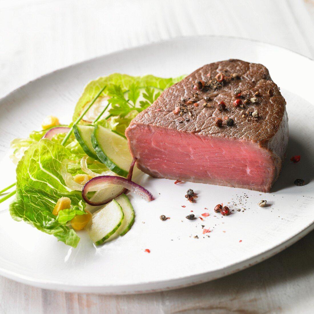 Medium rare pepper steak with a side salad