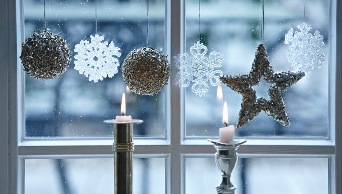 Christmas decorations and candles at a window
