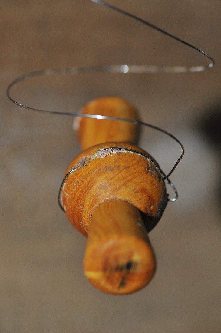 A wooden reel with a wire for cutting cheese