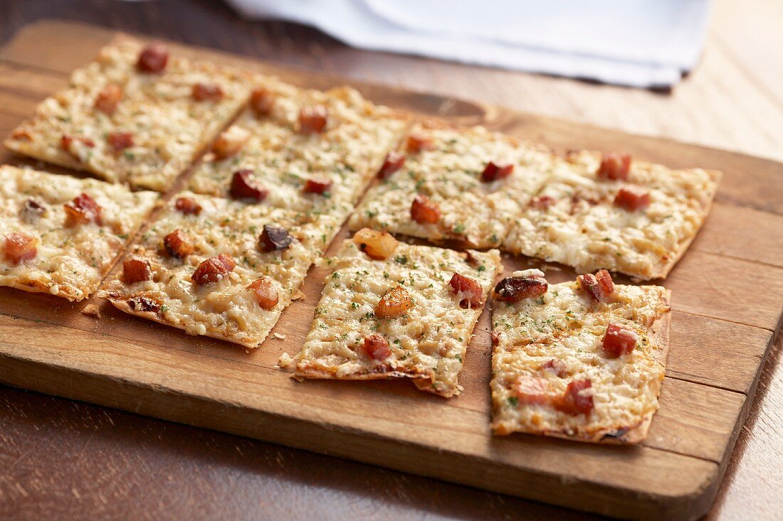 Flat Bread Pizza with Bacon; Cut Into Squares on a Cutting Board