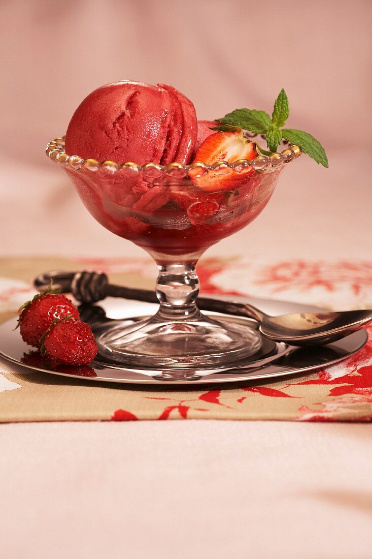 Glass Bowl of Strawberry Sorbet with Fresh Strawberries and Mint Garnish