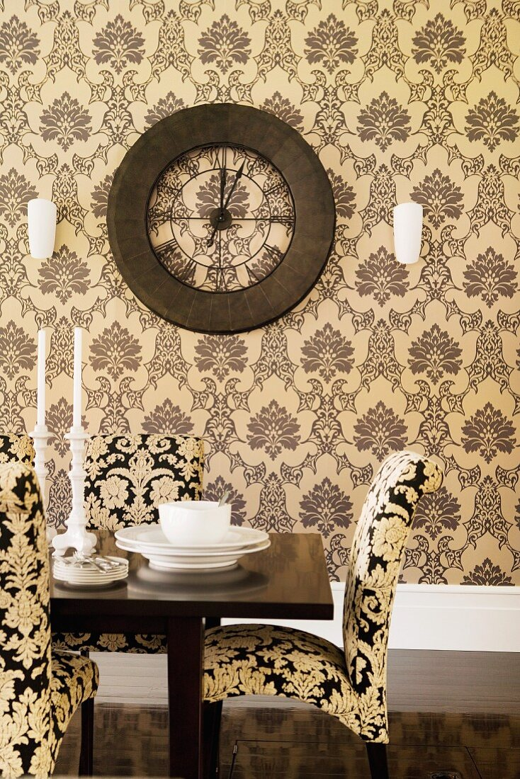 Chairs upholstered in ornamental patterned fabric at set table in front of patterned wallpaper and vintage wall clock