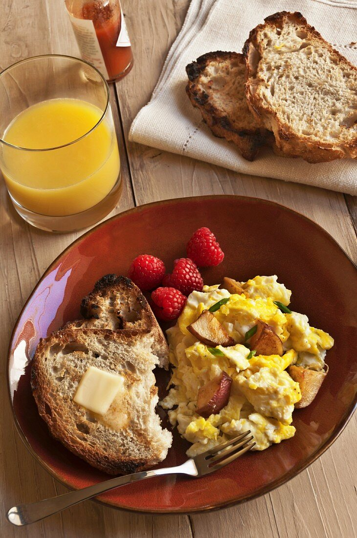 Eggs and Potatoes on a Plate with Buttered Toast and Raspberries; Orange Juice and Tabasco Sauce