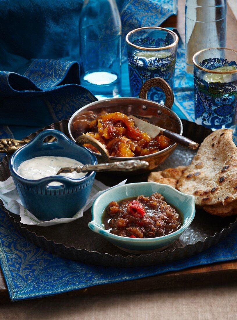 Indian side dishes: wholemeal roti, mango chutney, mint raita, tamarind and date chutney
