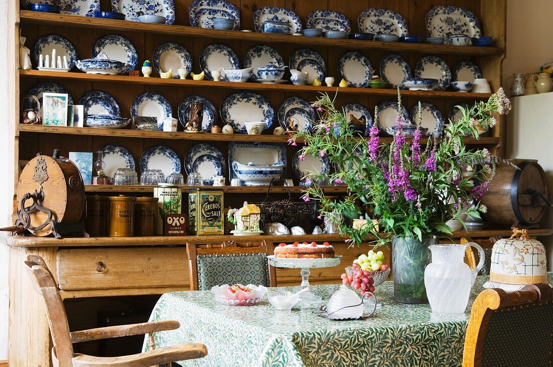Valuable collection of blue and white plates on wooden dresser and antique chairs around kitchen table