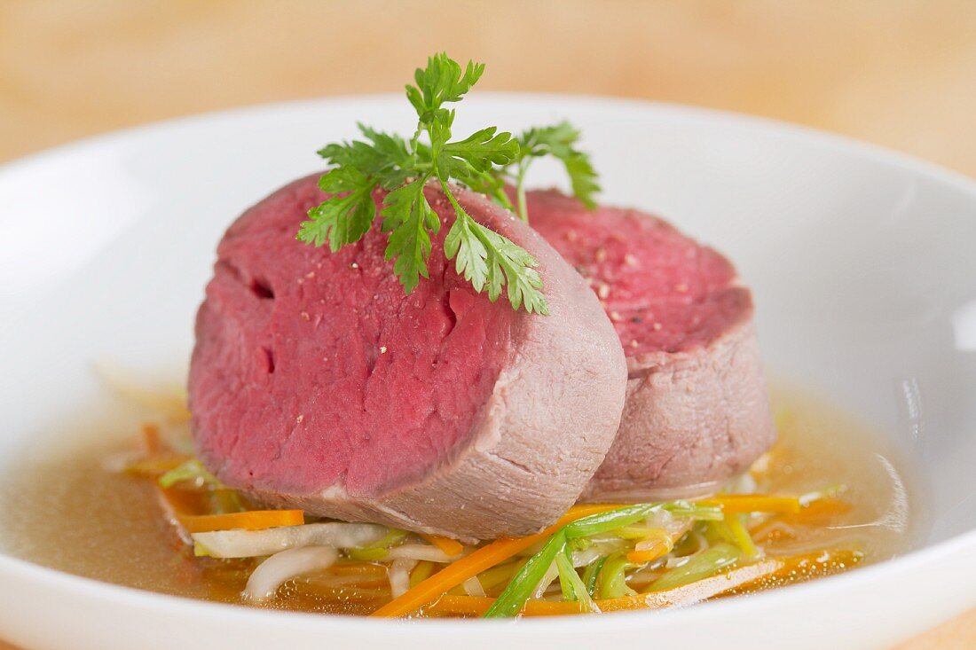 Poached fillet steak on a bed of vegetables with broth