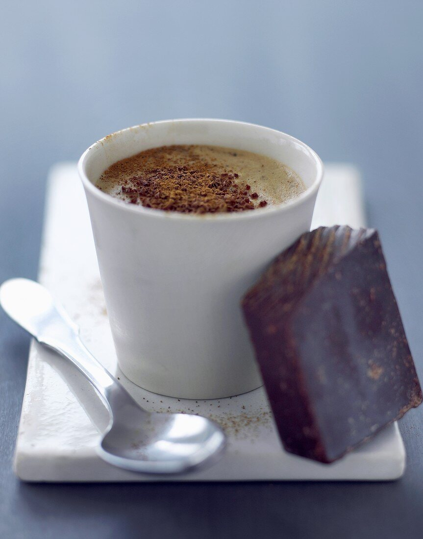 A cup of coffee and a piece of chocolate