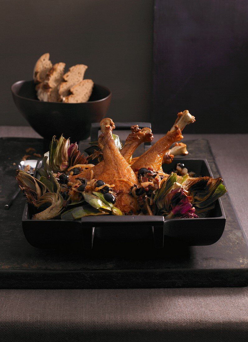 Goose legs with artichokes and olives