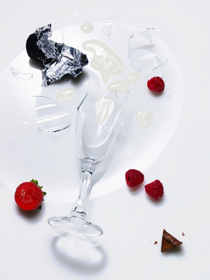 A broken champagne glass and berries