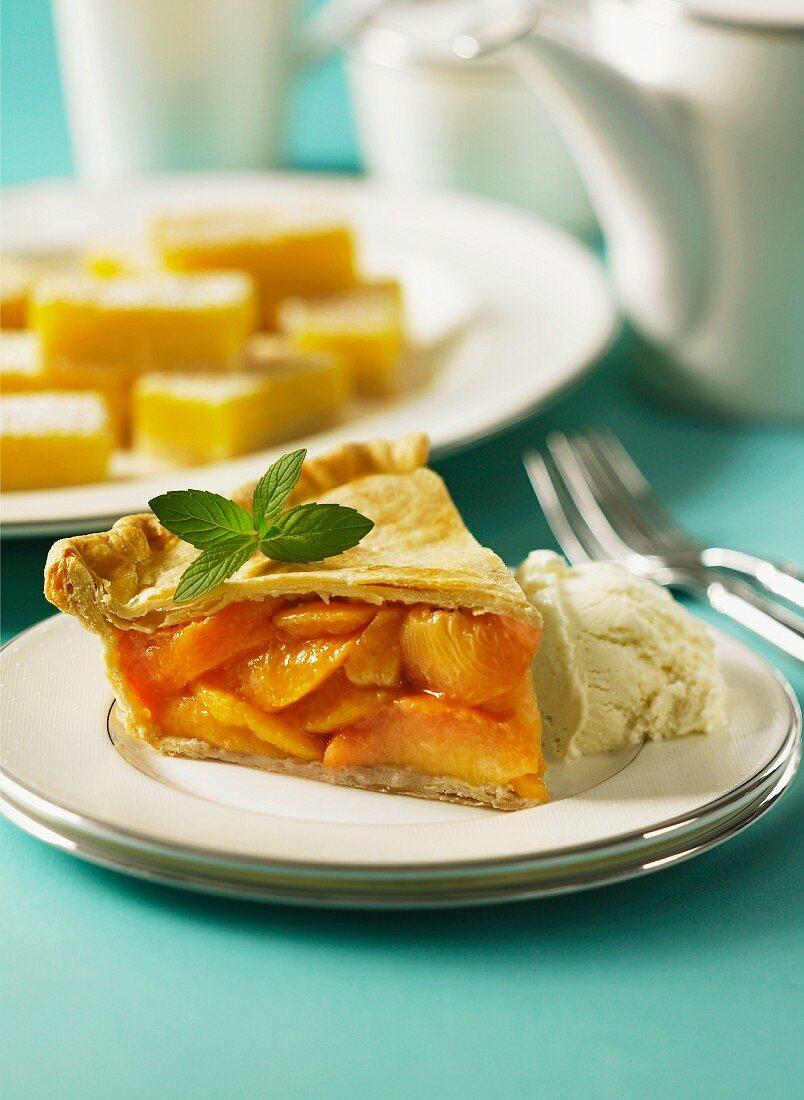 A slice of peach pie with vanilla ice cream and lemon wedges