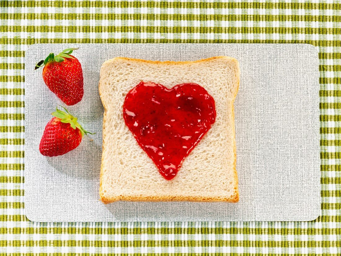 A heart-shaped dollop of jam on a slice of toast