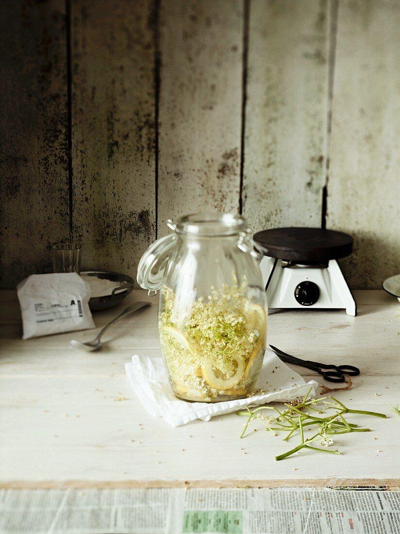 Elderflowers and lemon slices in a preserving jar