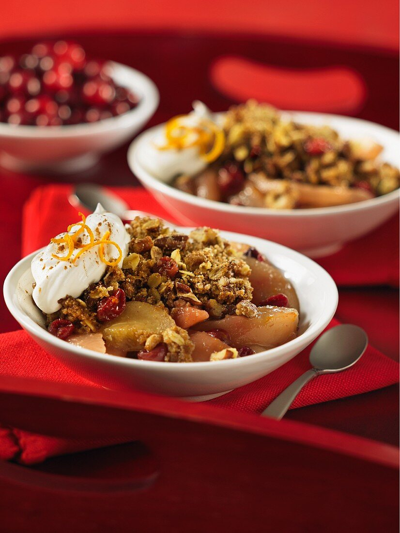 Pear and cranberry crumble with pecan nuts and cream