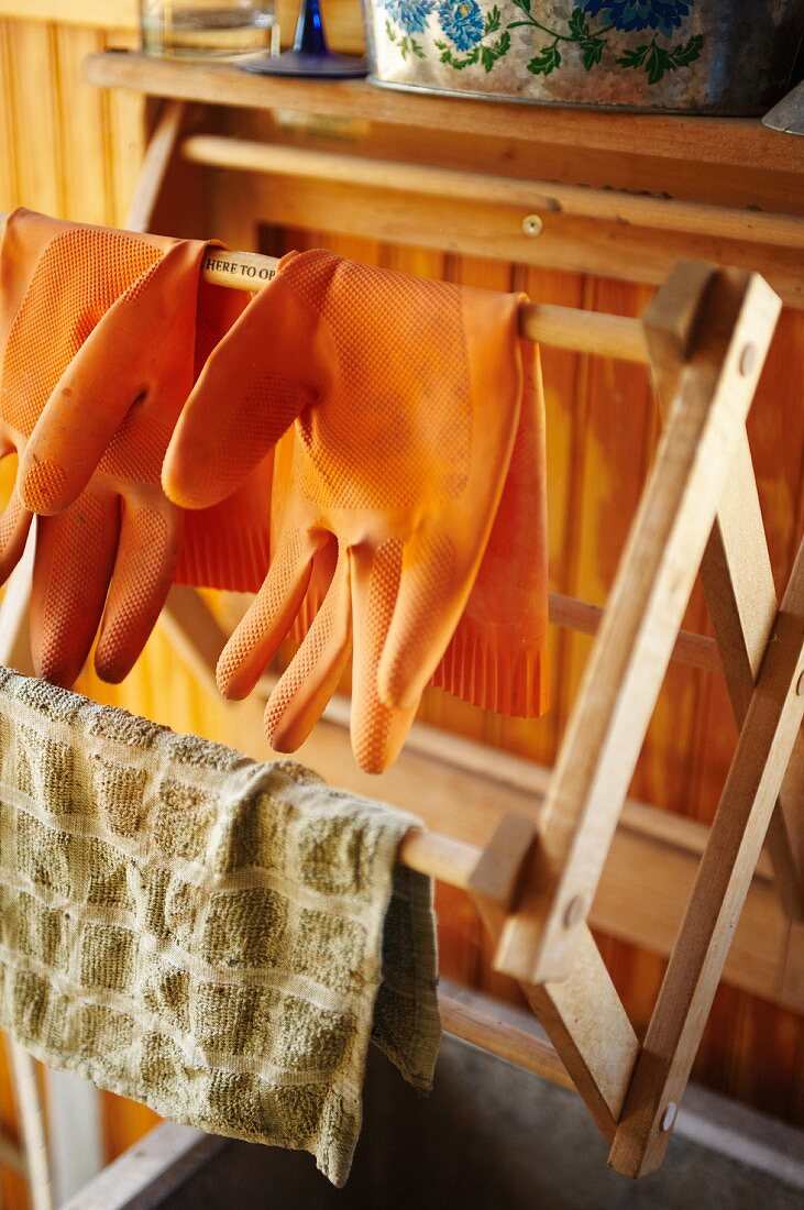 Wooden Drying Rack with Rubber Gloves and a Dish Towel
