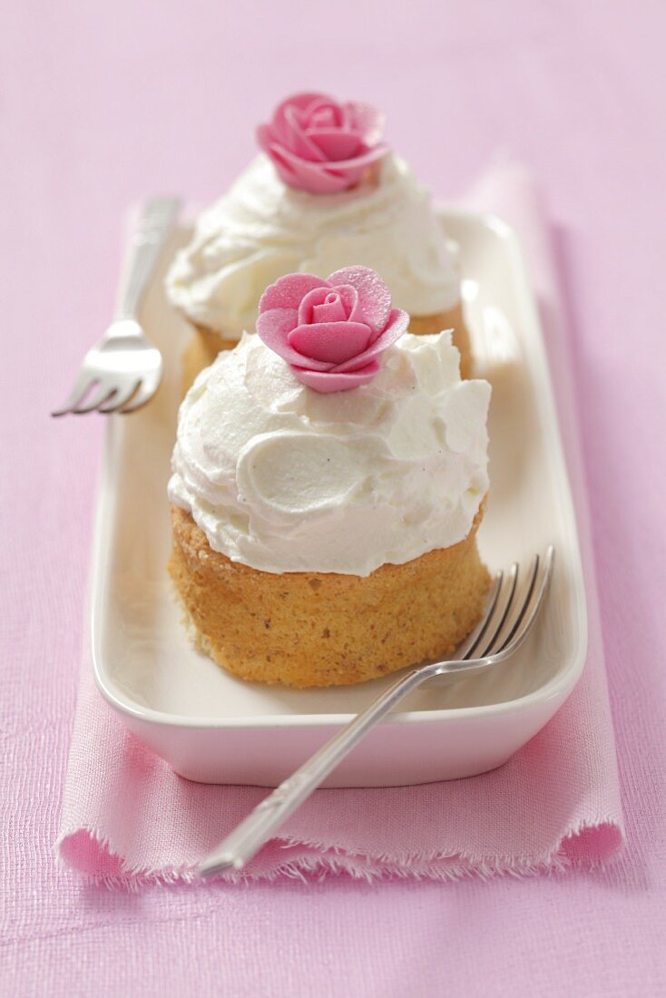 Mini sponge cakes topped with vanilla cream and sugar flowers