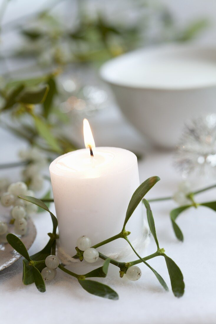 A white candle with mistletoe