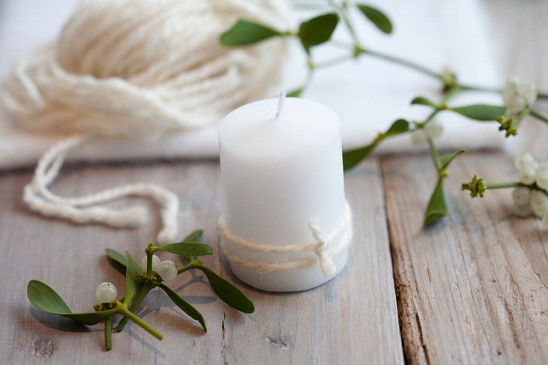 Mistletoe being tied to a candle