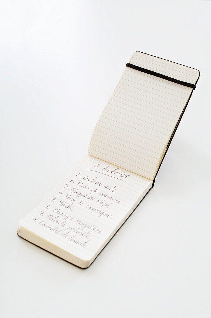 A shopping list written in a notebook