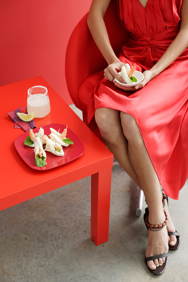 A woman wearing a red party dress sitting a small table with prawn sandwiches and a cocktail