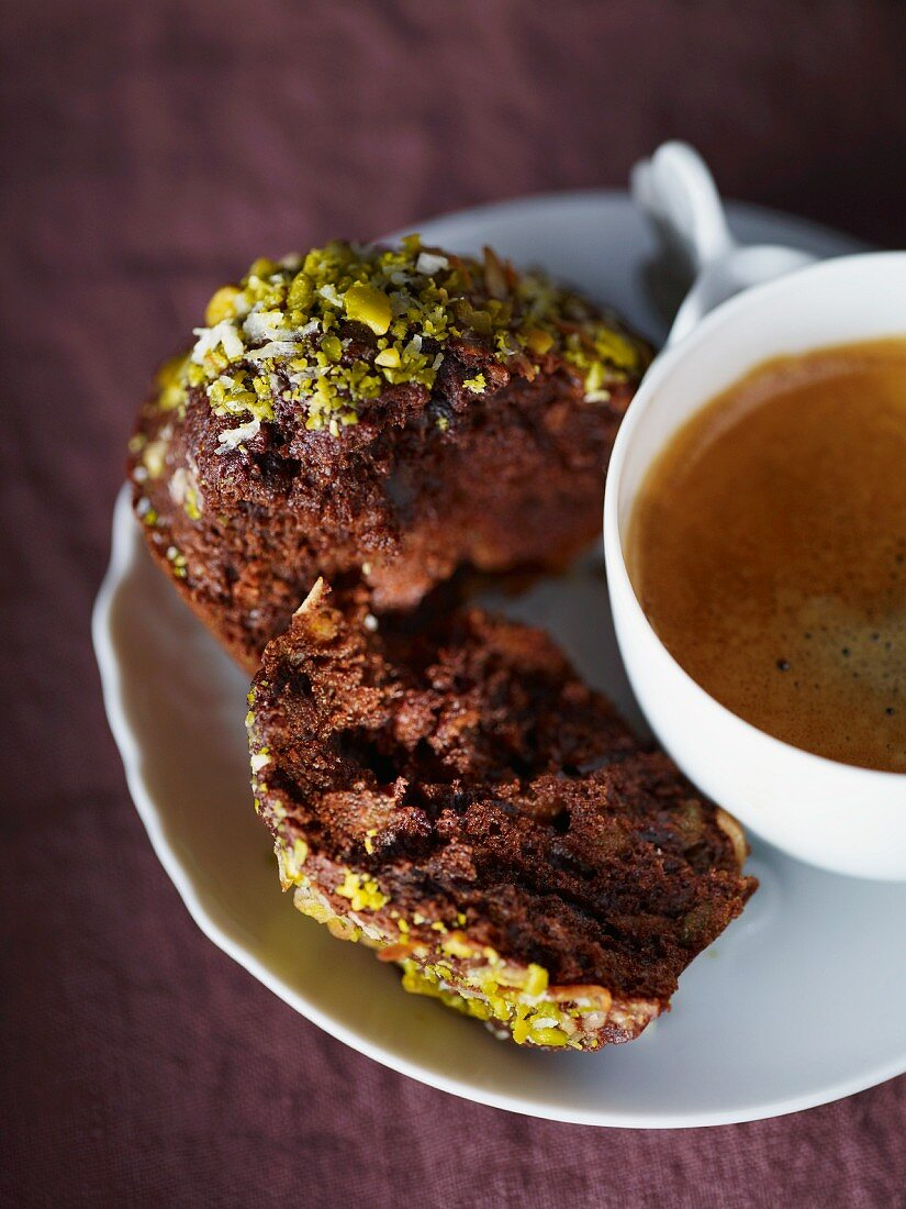 Mini chocolate and coconut cakes with pistachios and a cup of coffee
