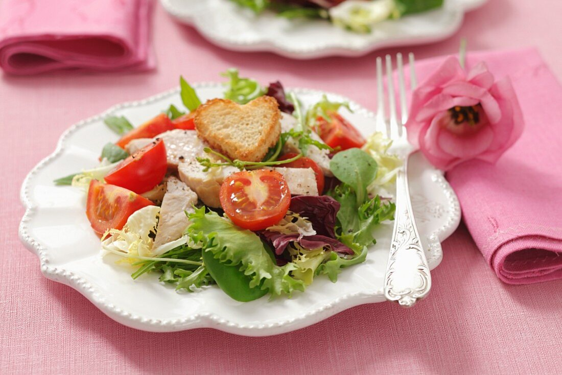Green salad with cherry tomatoes, grilled chicken breast and heart shaped croutons
