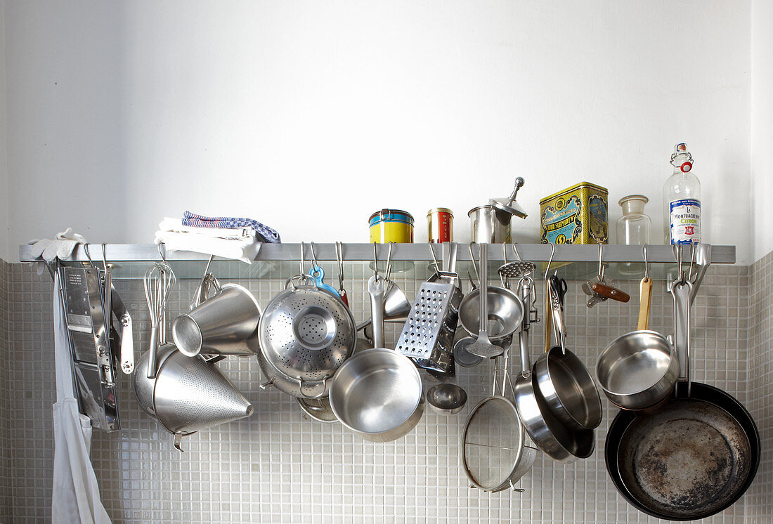 Various stainless steel pots and pans hanging from wall-mounted shelf