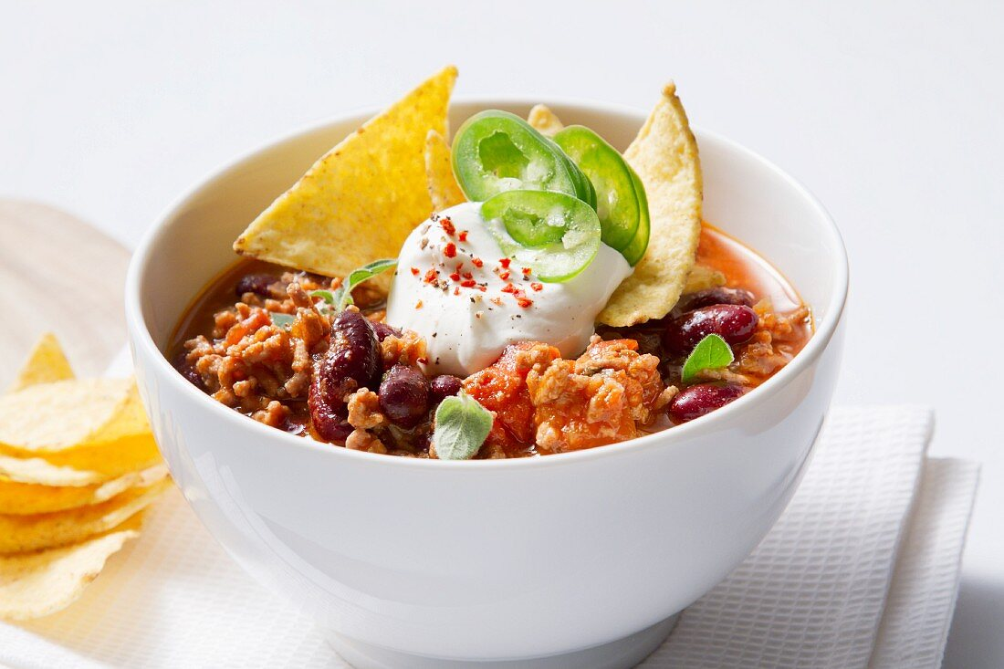 Chili con carne with sour cream and tortilla chips