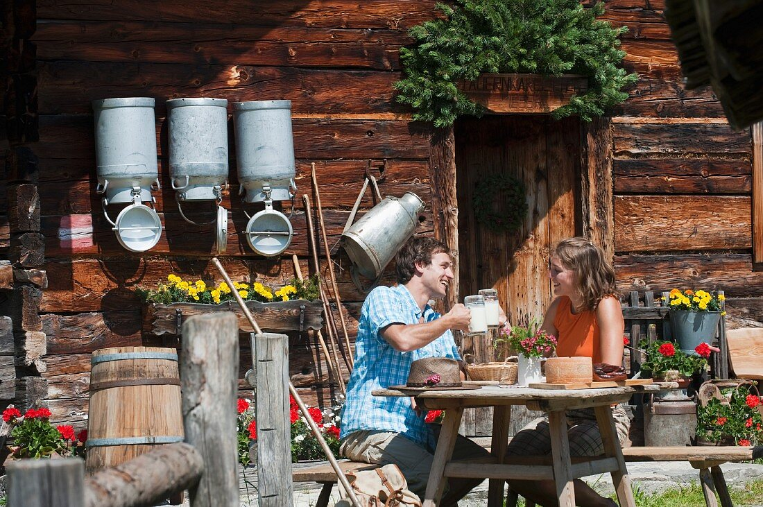 A young couple eating in front of an alpine hut