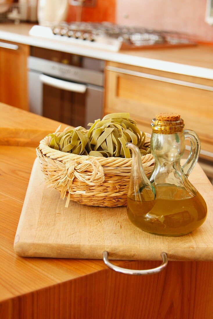 Tagliatelle in a basket and olive oil in a glass jug