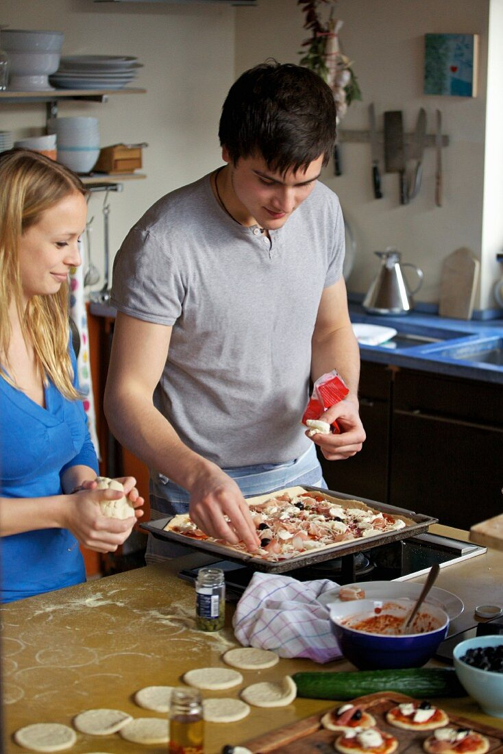 A young woman and the young man making pizza