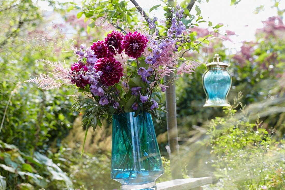 A bunch of summer flowers and a lantern in a garden