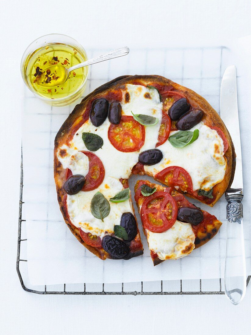 Tomato, Olive Basil Pizza; One Slice Partially Removed; From Above
