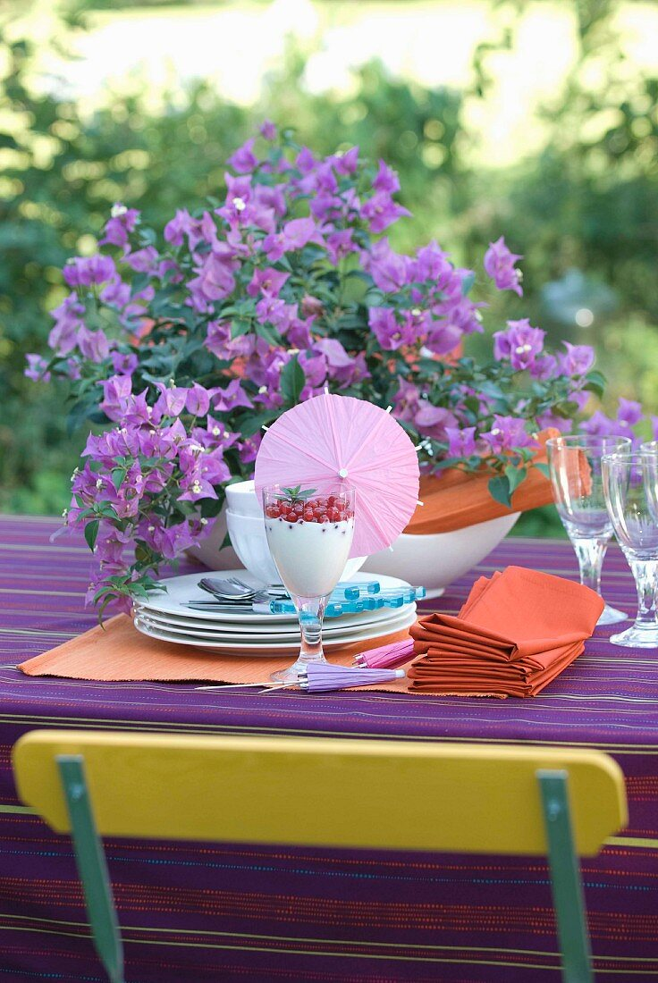 Preparations for a summery garden table set with bougainvillea on a purple tablecloth and back of chair in the complementary colour of yellow