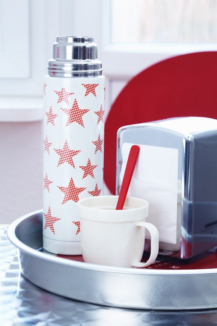 A Thermos flask decorated with stars, a spoon and a napkin dispenser on a tray