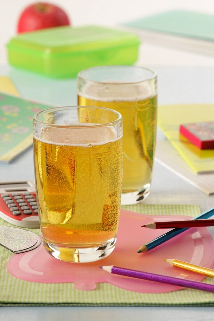 Two glasses of sparkling apple juice with school things
