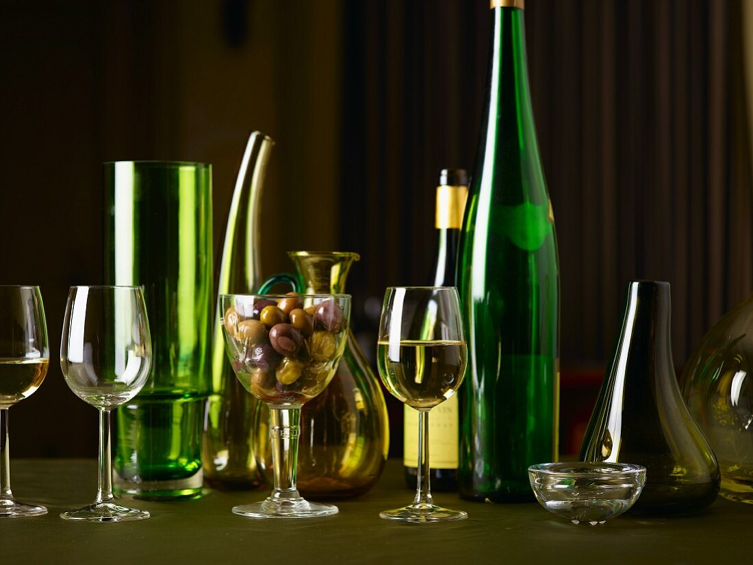 White wine glasses, wine bottles, carafes and olives