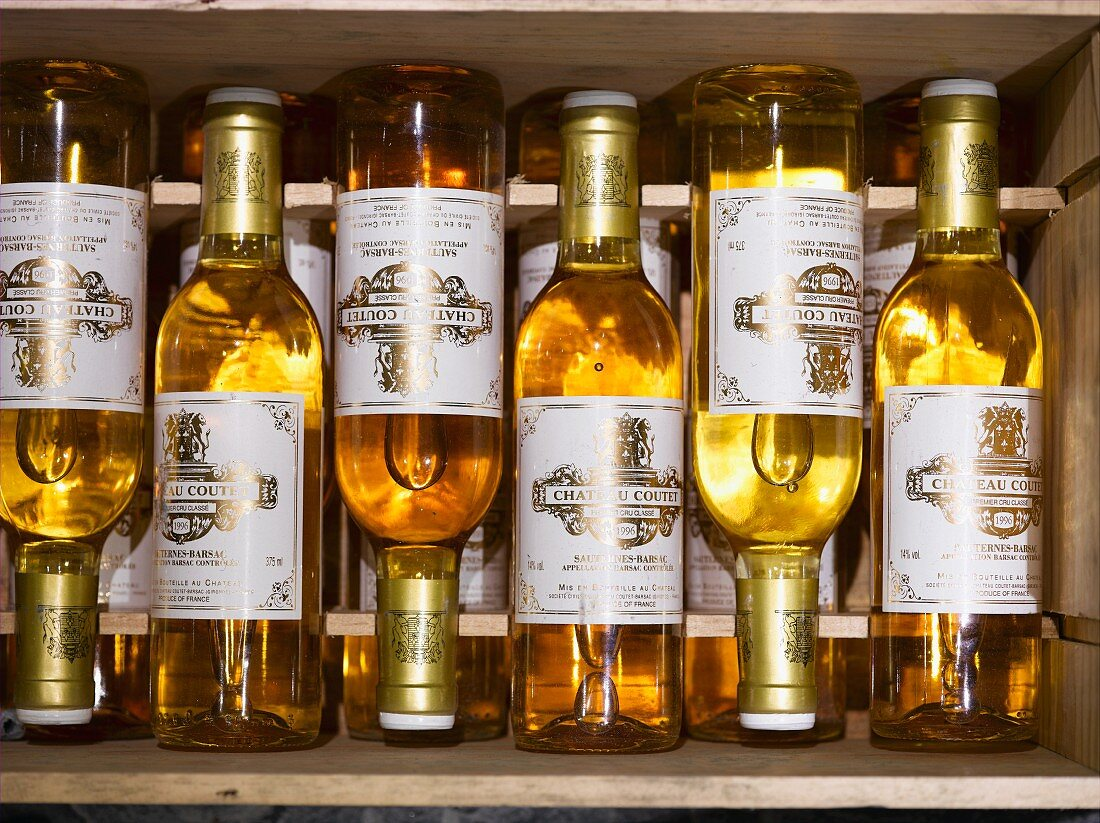 Stickered white wine bottles in a wooden crate (seen from above)