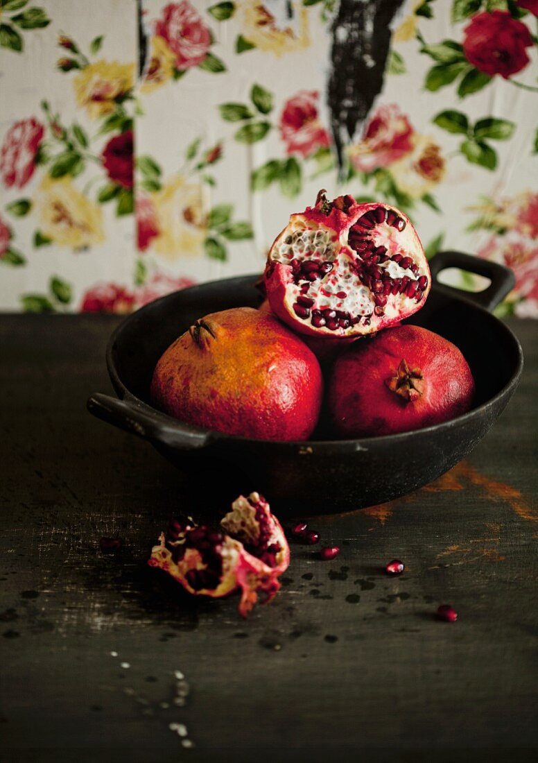 Pomegranates, whole and sliced, in a bowl