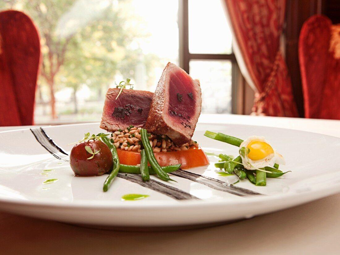 Pan Seared Yellowfin Hawaiian Tuna, Haricot Vert, Farro, Heirloom Tomatoes, Squid Ink, Fried Quail Egg, and Black Lava Sea Salt