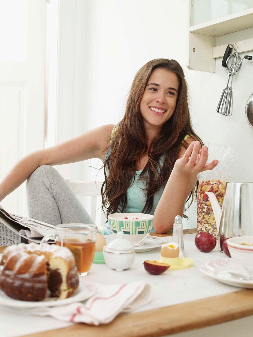 A young woman having breakfast with marble cake