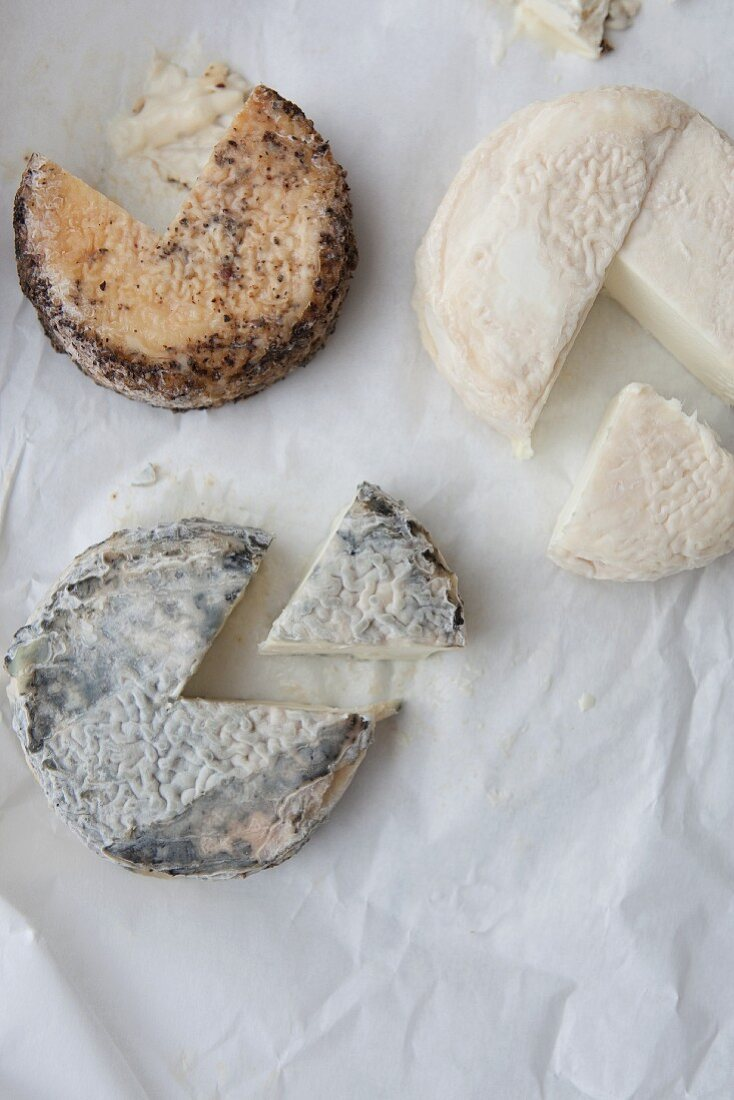 Three Assorted Goat Cheese Wheels; Each with a Wedge Removed; From Above