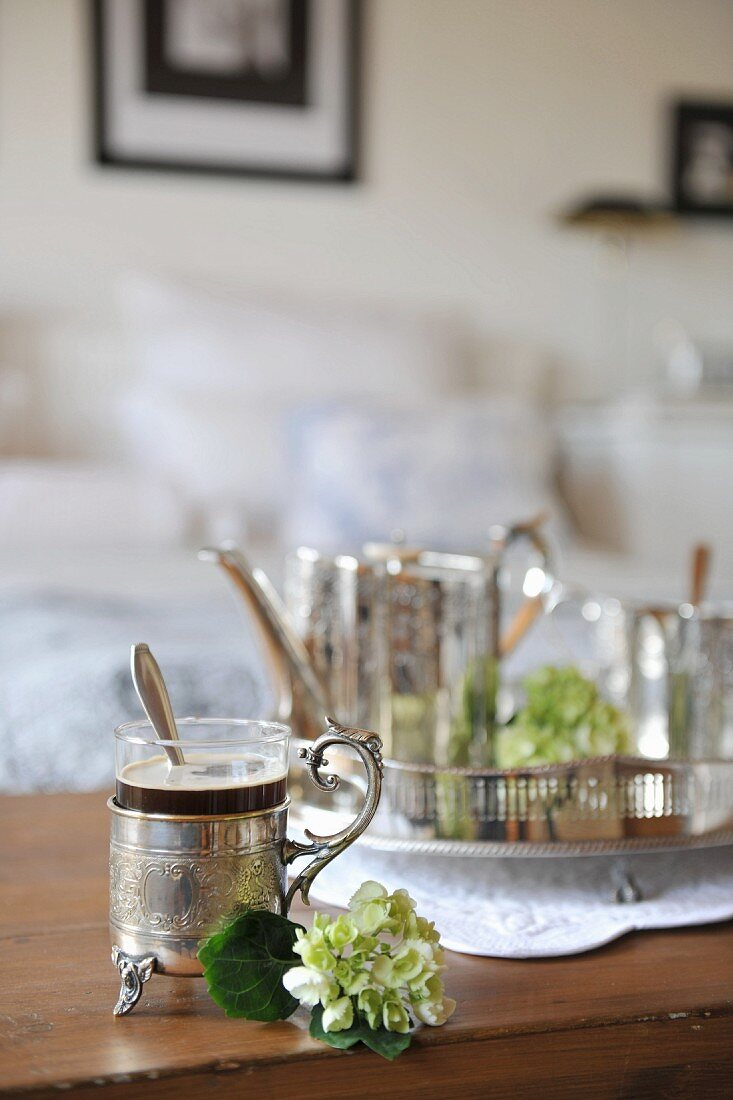 Coffee in a glass with decorated silver holder and handle next to a white flower in front of a tray with a silver service