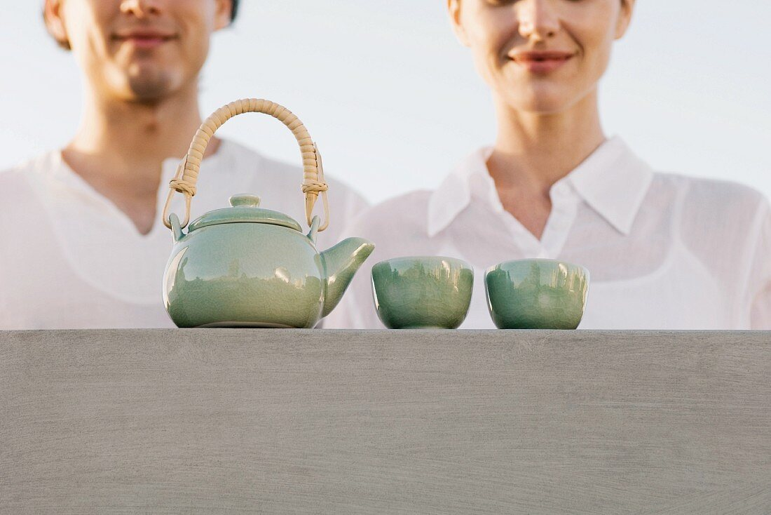 Teapot and tea cups sitting on ledge, cropped view of man and woman waiting nearby