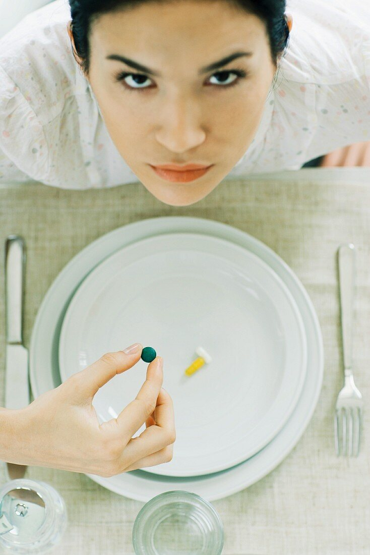 Woman sitting at empty plate holding vitamin, looking up at camera