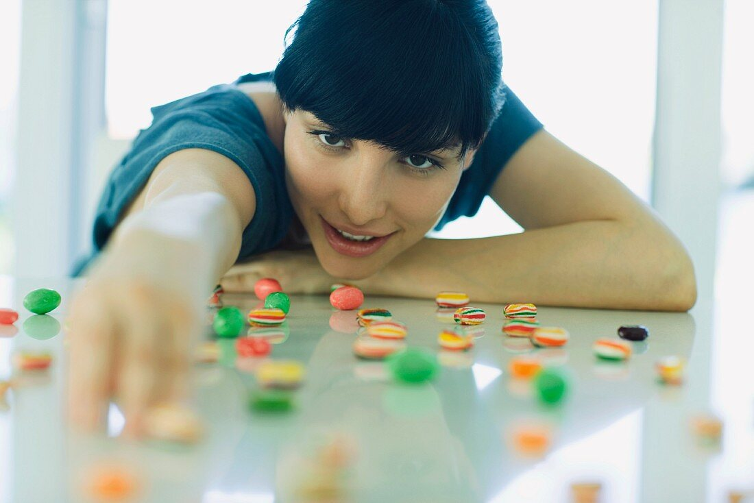 Table spread with candy, woman resting head on arms, reaching for piece of candy
