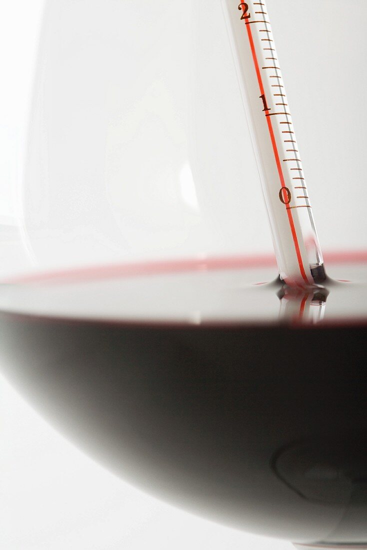Thermometer in glass of red wine, extreme close-up