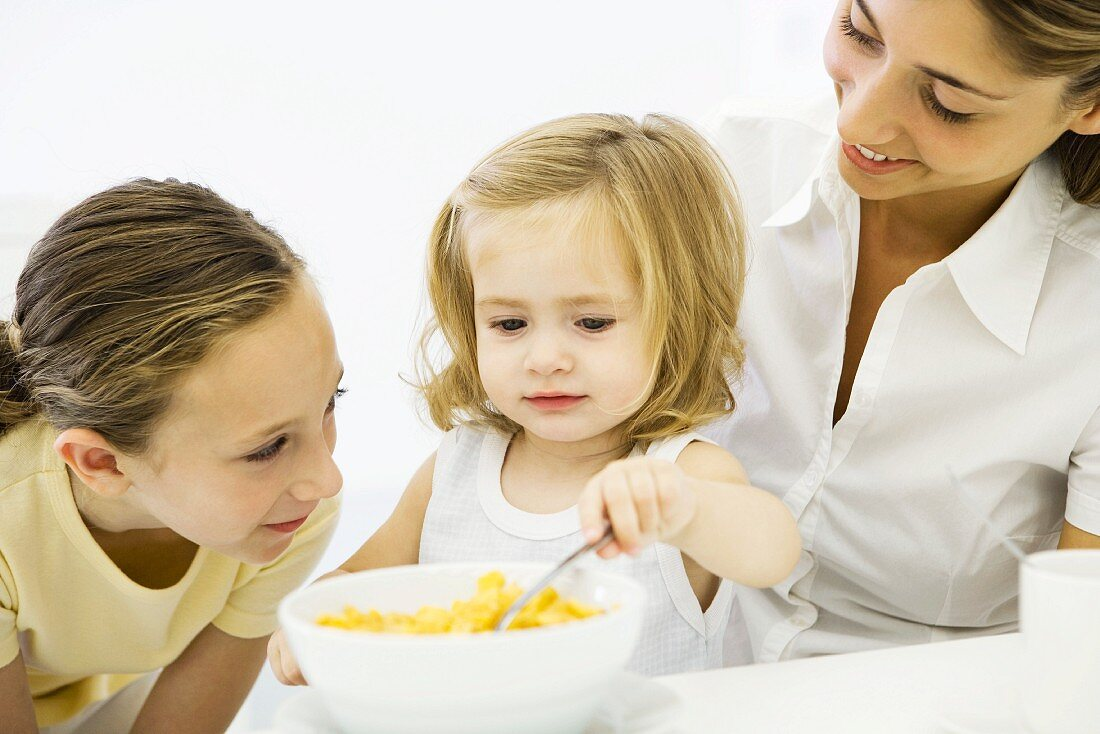 Little girl eating cereal, older sister and mother watching