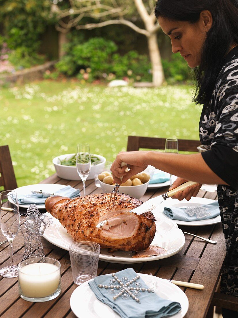 A woman carving larded roast ham on a table in a garden