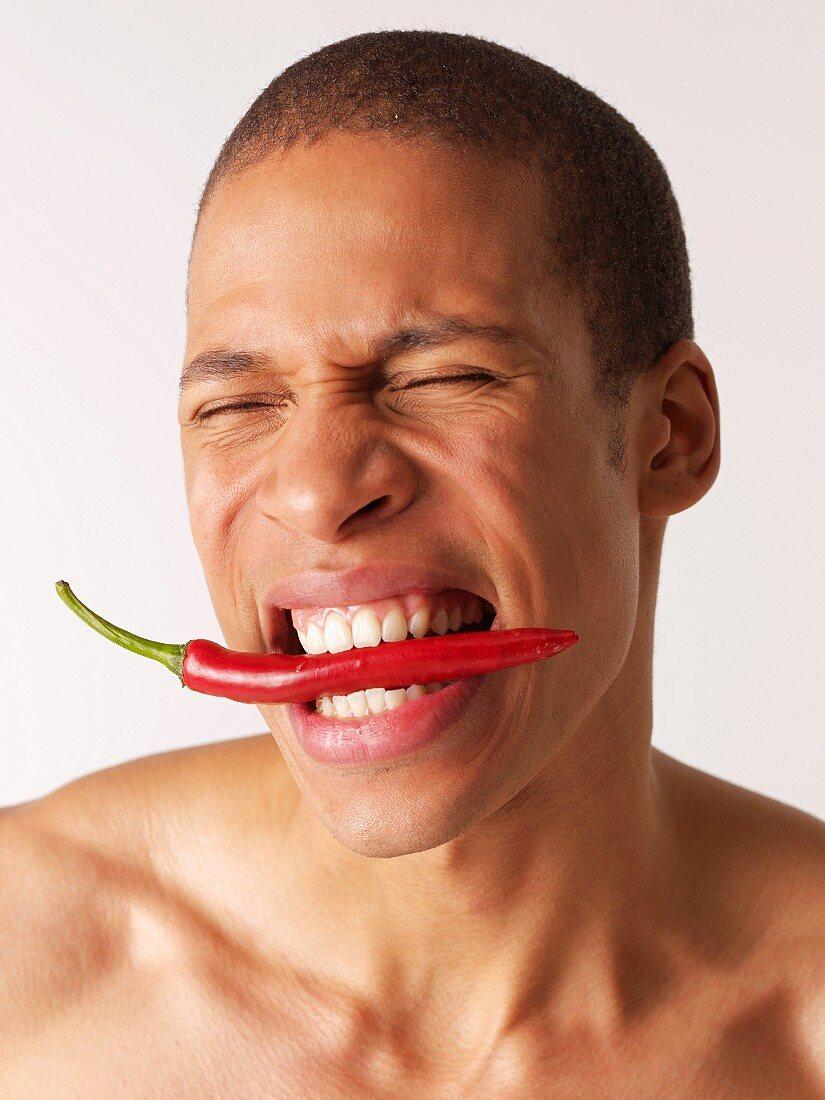 Man biting on hot pepper