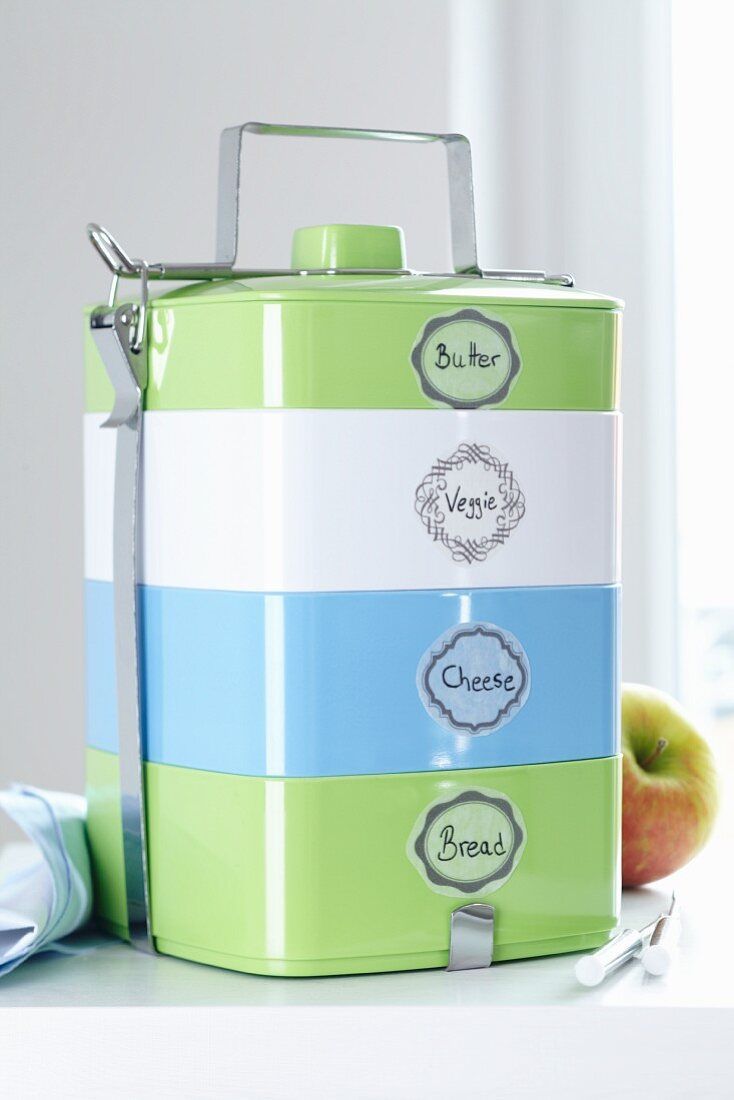 Retro-styled stacking boxes as a lunchbox with handwritten labels made from masking tape